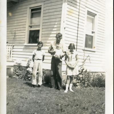 Gwen Ketchum and family members stand in front of a house