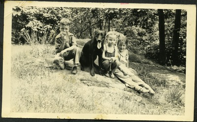 Gwen Ketchum sits with childhood friends and a dog in a park