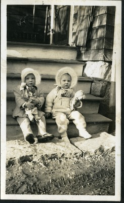 Gwen Ketchum and a childhood friend play with dolls on porch steps