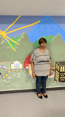 Rosebud Davis in front of the MLK Jr. Apartments mural