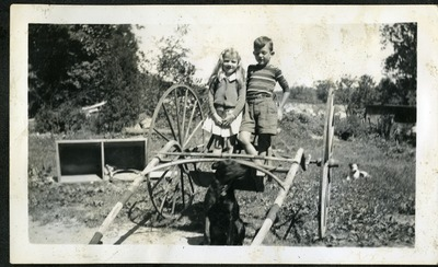 Gwen Ketchum stands with her brother next to farm equipment and a dog