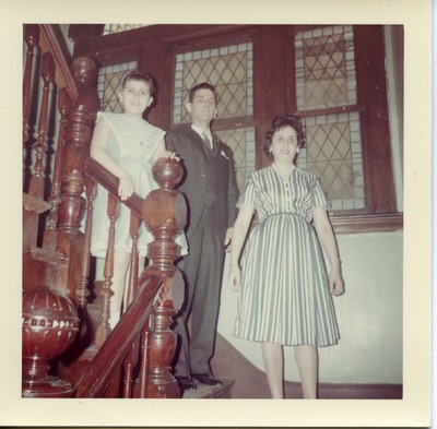 Miriam Arrango standing on a staircase with her parents
