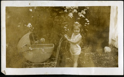 Gwen Ketchum as a child playing with a baby carriage