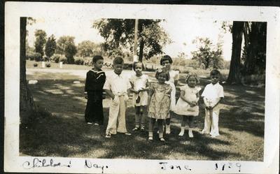 Gwen Ketchum poses with children on Children's Day